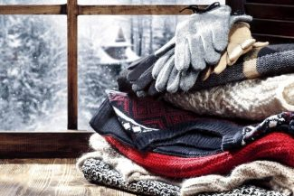 Stack of sweaters and gloves in front of a frosted windowpane