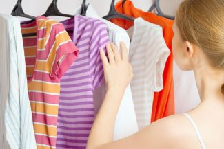 Girl looking through clothes in her closet