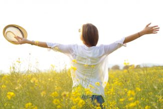 Woman among yellow flowers opening her arms in the sun