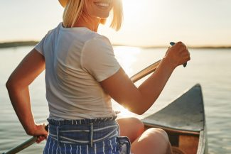 Woman riding canoe into the sunset